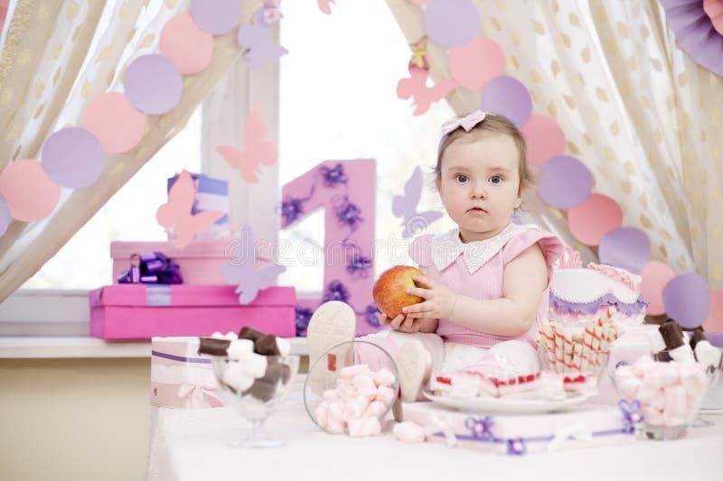 Behandla som ett barn flickan som firar den första födelsedagen arkivfoto