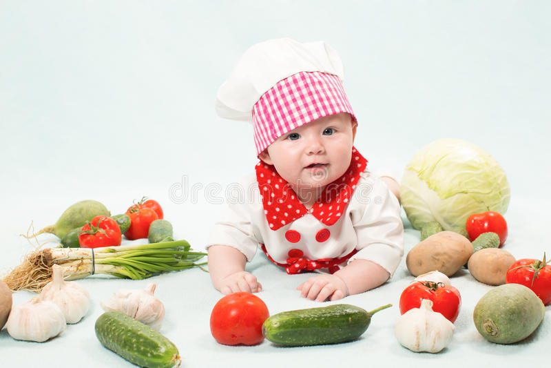 Behandla som ett barn flickan som ha på sig en kockhatt med grönsaker arkivbilder