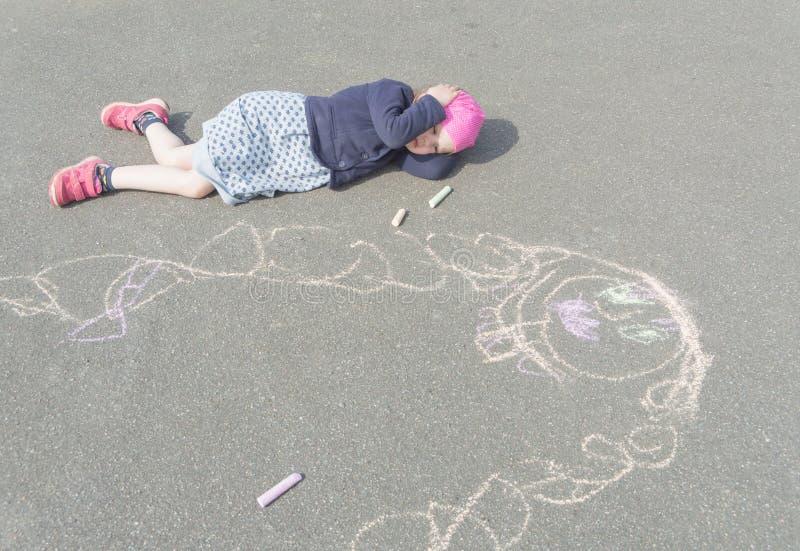 Behandla som ett barn flickan som ligger på trottoaren som tänker om mamma arkivfoto