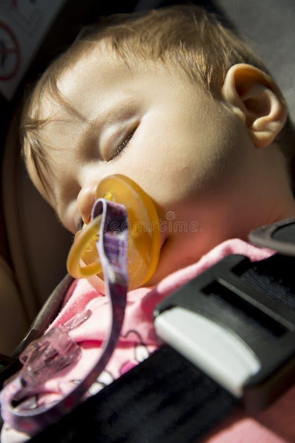 Behandla som ett barn flickan som sover i bilsätet royaltyfria foton