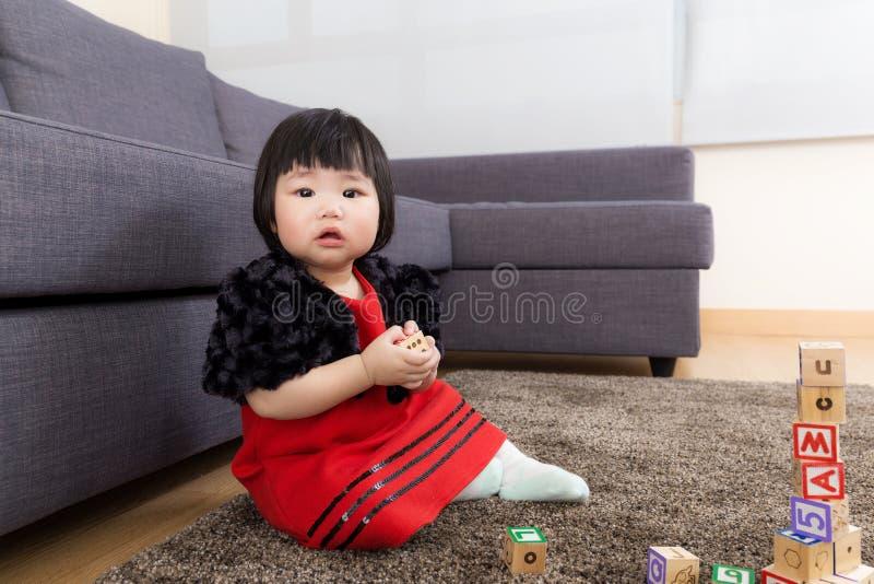 Behandla som ett barn flickan som spelar träkvarter royaltyfria bilder