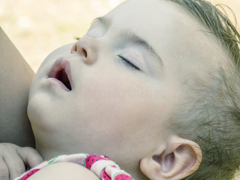 Behandla som ett barn flickan sover i mother& x27; s-armar, utomhus royaltyfri fotografi