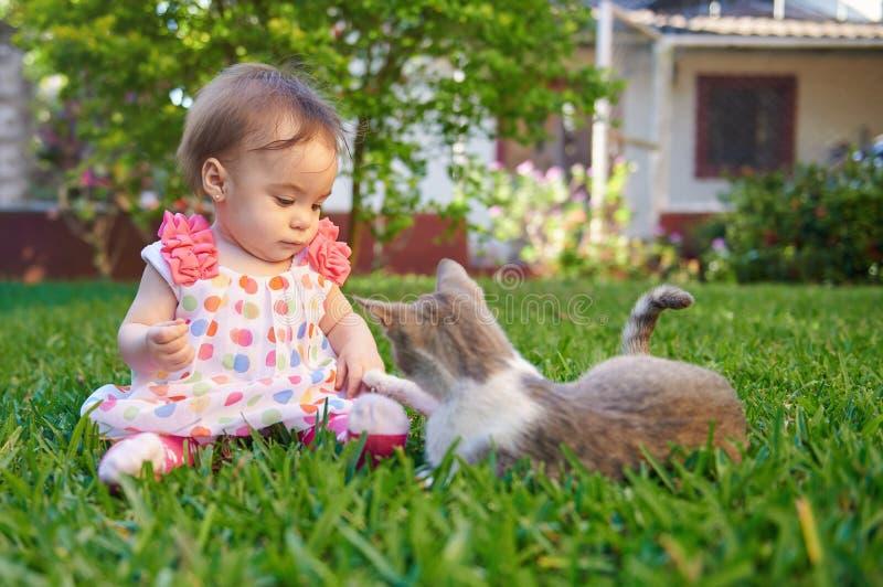 Behandla som ett barn flickan som spelar med katten arkivbild