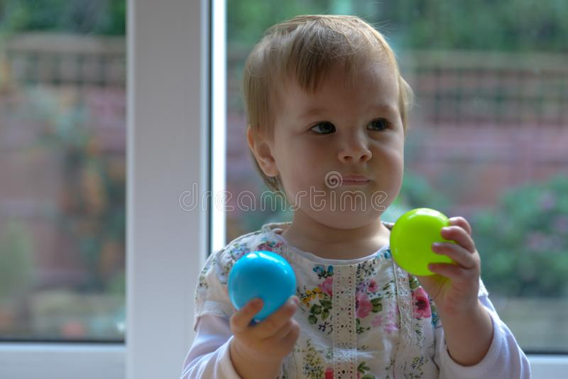 Behandla som ett barn flickan som spelar med kulört le för bollar royaltyfri bild