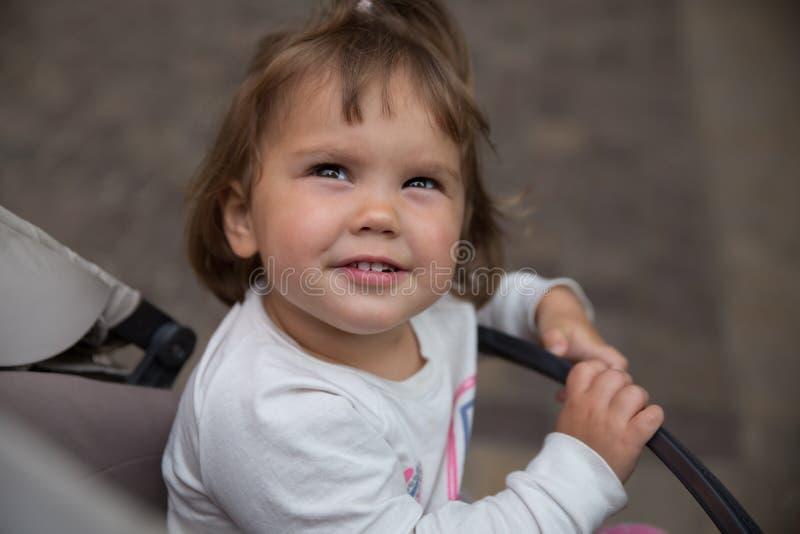 Behandla som ett barn flickan utanf?r att sitta i en sittvagn royaltyfria bilder