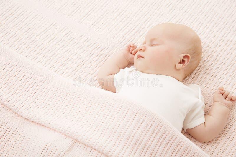 Behandla som ett barn flickasömn i säng som sover det nyfödda barnet på rosa färgfilten royaltyfri foto