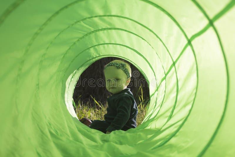 Behandla som ett barn flickasammanträde i Toy Tunnel arkivfoton