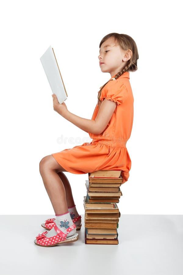 Behandla som ett barn flickasammanträde på böcker som läser en bok fotografering för bildbyråer