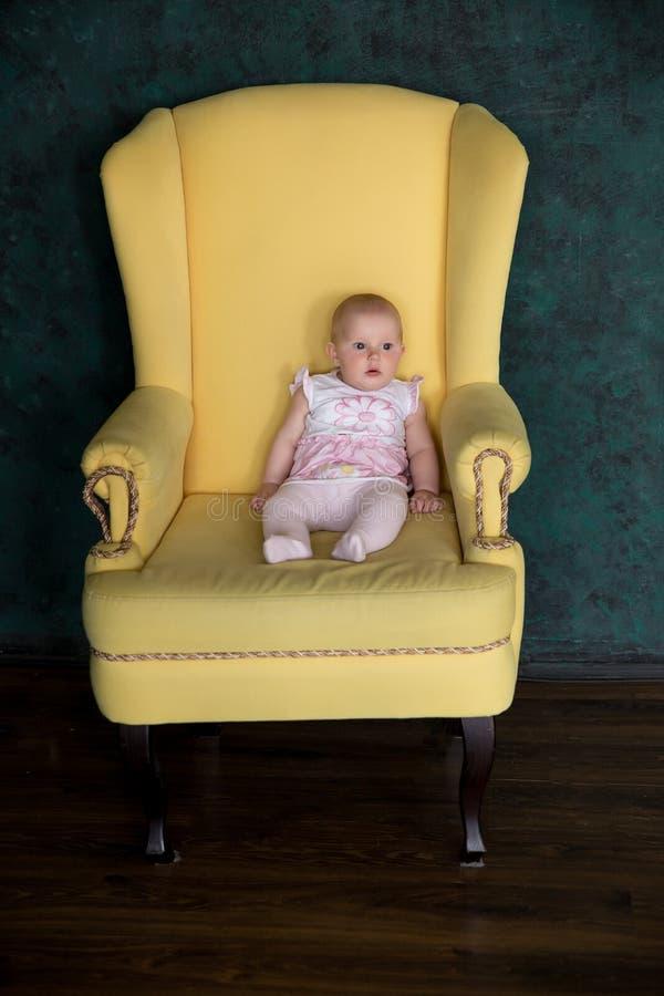 Behandla som ett barn flickasammanträde på den stora fåtöljen i studio arkivbilder