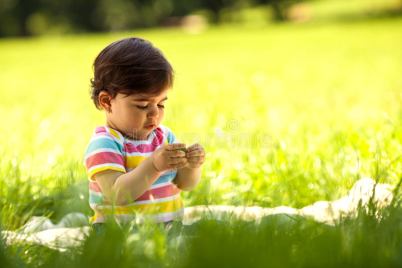 Behandla som ett barn flickasammanträde på gräs och att spela royaltyfri foto