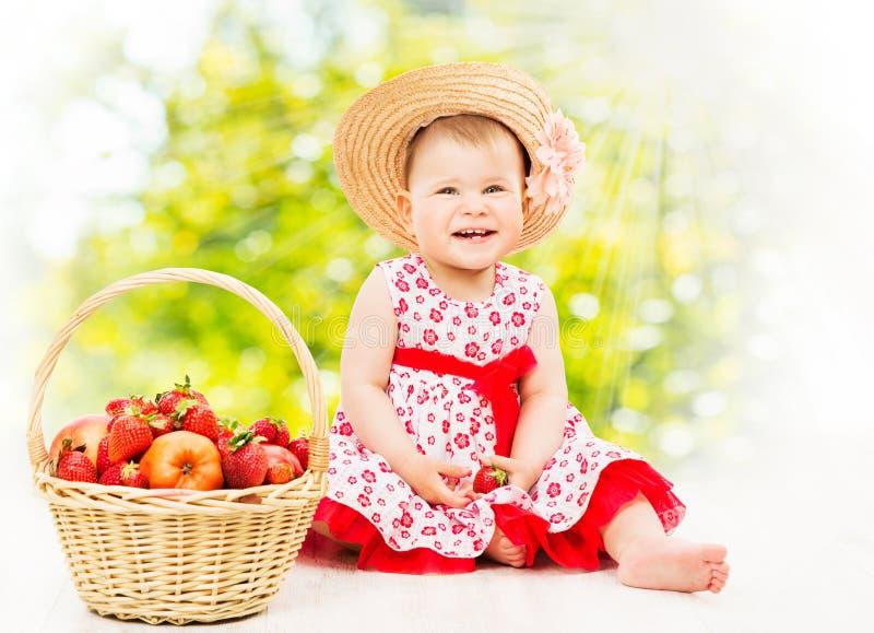 Behandla som ett barn flickast?enden, lycklig unge i sommarmodekl?nningen Straw Hat With Basket Full av jordgubben royaltyfri bild