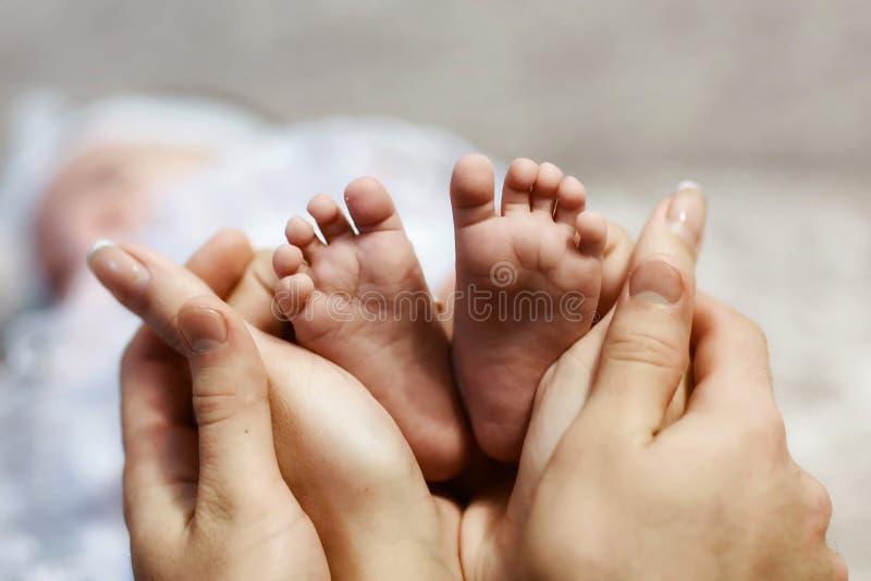 Behandla som ett barn fot i moderhänder, mycket litet nyfött behandla som ett barn fot för ` s på kvinnlign formade händer closeu fotografering för bildbyråer