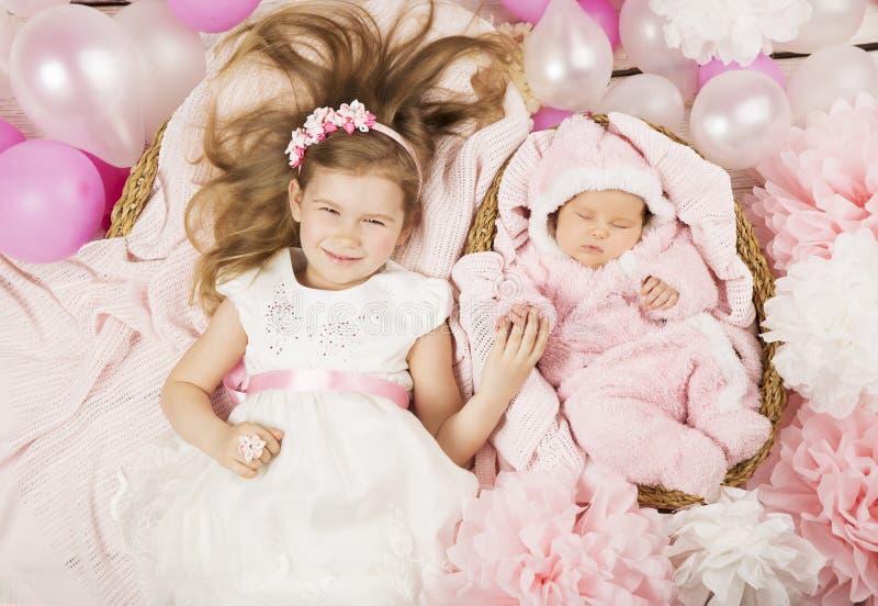 Behandla som ett barn gåvor för födelsedagpartiet Flicka som rymmer den nyfödda systerhanden chi fotografering för bildbyråer