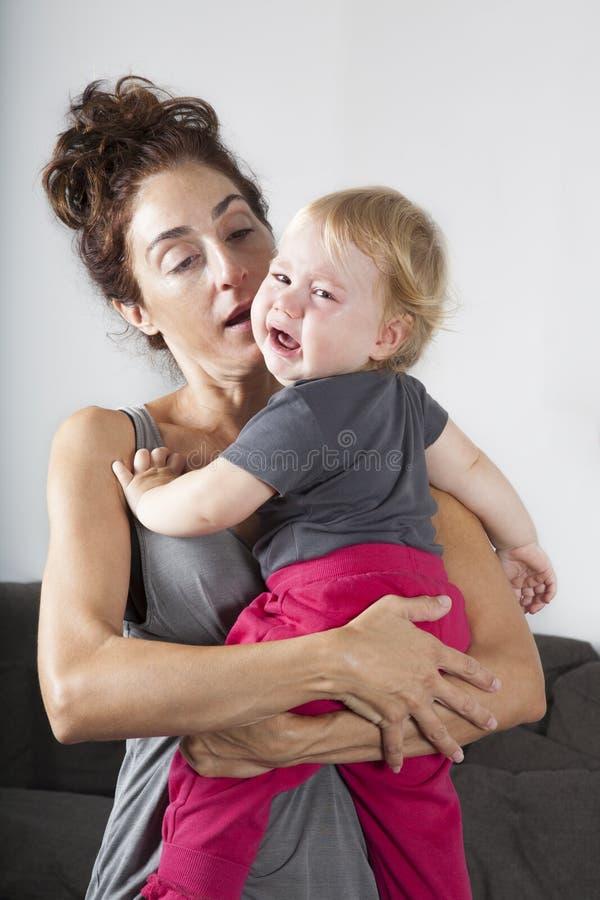 Behandla som ett barn gråt i mammaarmar arkivfoto