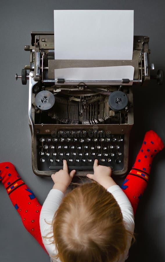 behandla som ett barn gulligt litet skrivmaskinsskrivande fotografering för bildbyråer