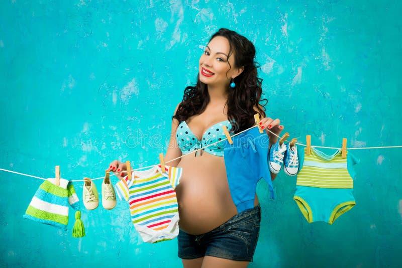 Behandla som ett barn hängande kläder för lycklig gravid kvinna inför framtiden behandla som ett barn att vänta Klämma fast utfor fotografering för bildbyråer