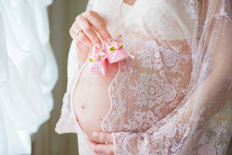 Behandla som ett barn hållande rosa färger för gravid kvinna skor på hennes buk royaltyfri foto
