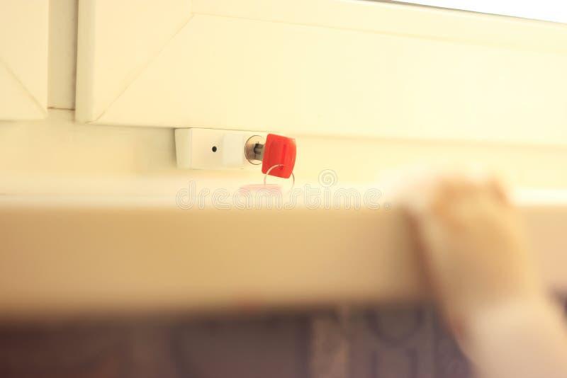 Behandla som ett barn handen för ` s och säkra fönsterhandtaget med tangent låsa på fönstret för skydd från barnet du kan bläddra arkivbild
