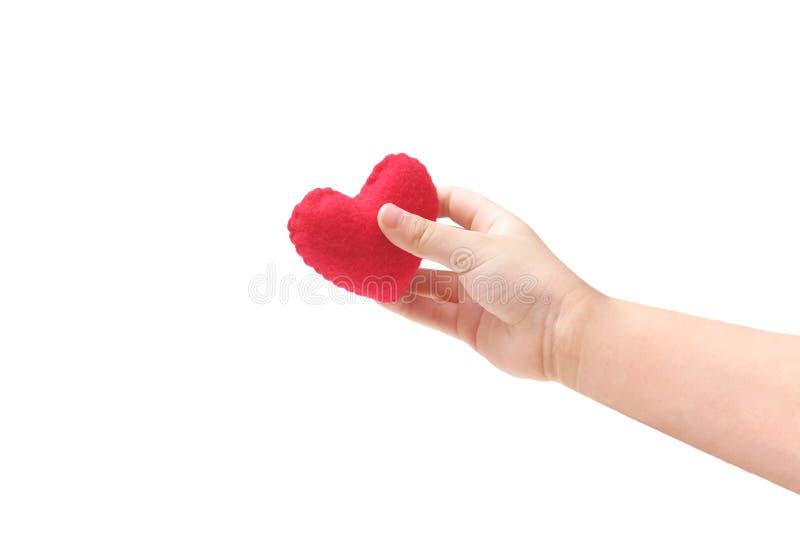 Behandla som ett barn handen för ` som s rymmer en röd hjärta royaltyfri fotografi