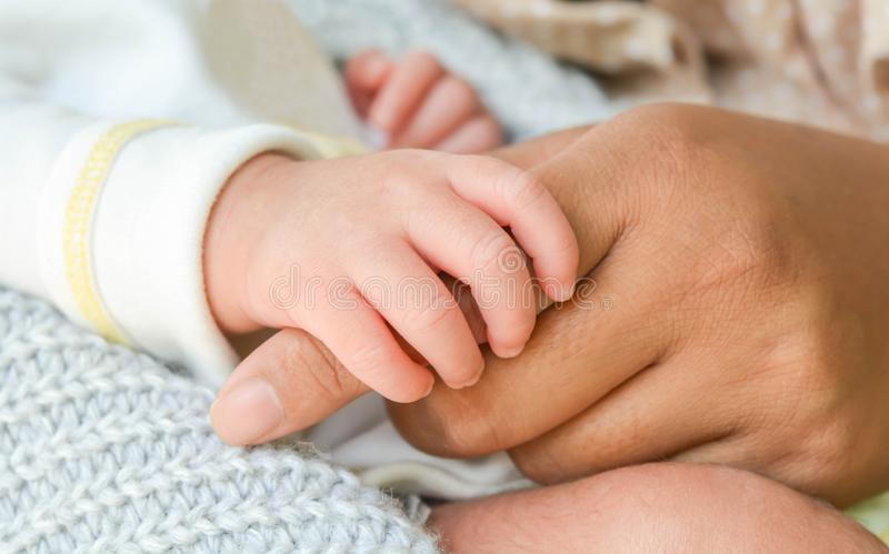 Behandla som ett barn handen som rymmer moderns hand arkivbild
