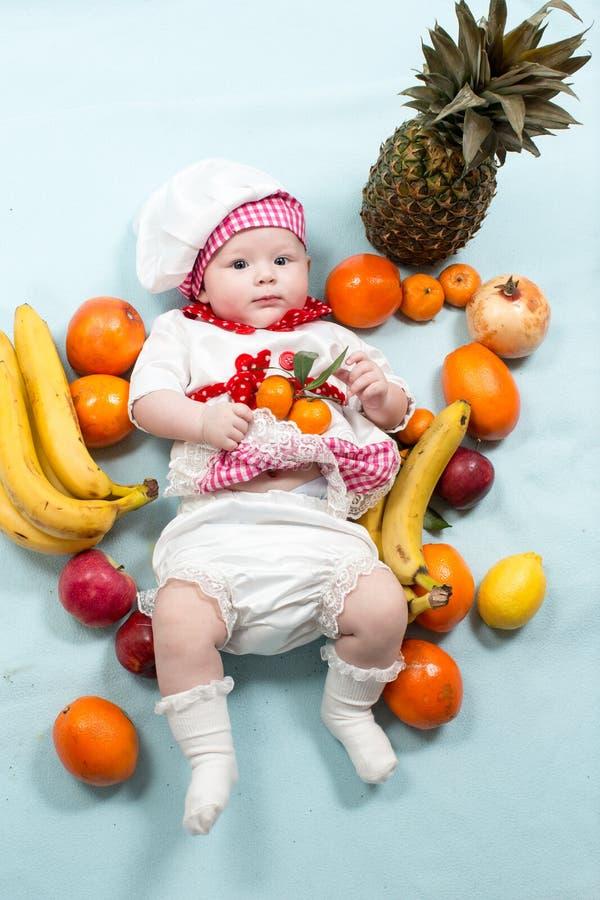 Behandla som ett barn hatten för kocken för kockflickan den bärande med nya frukter royaltyfria foton