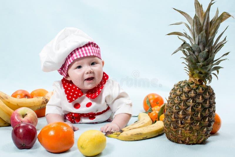 Behandla som ett barn hatten för kocken för kockflickan den bärande med nya frukter arkivbild