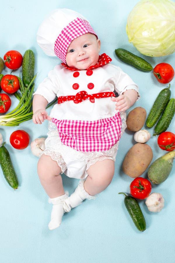 Behandla som ett barn hatten för kocken för kockflickan den bärande med nya grönsaker. royaltyfria bilder
