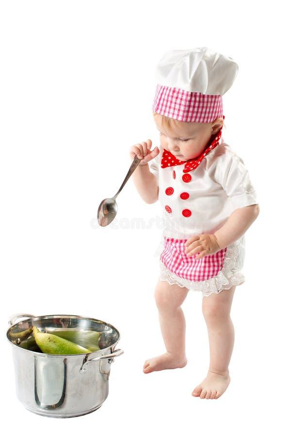Behandla som ett barn hatten för kocken för kockflickan den bärande med nya grönsaker och frukter. royaltyfri foto