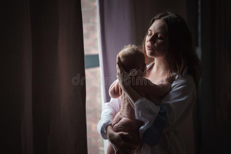 behandla som ett barn henne som kramar moderbarn arkivfoto