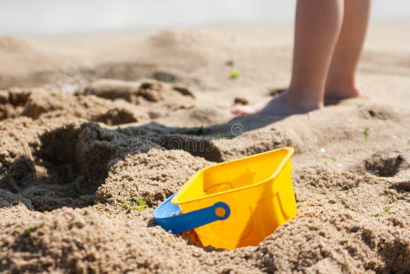 Behandla som ett barn hinken på en sandig strand i bakgrunden royaltyfri bild