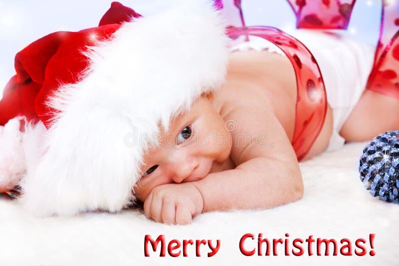 Behandla som ett barn i en stor jultomtenhatt arkivfoto