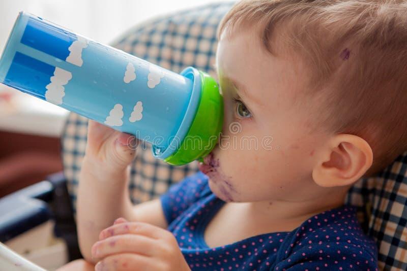 Behandla som ett barn i köket som dricker fruktsaft eller, mjölka, vitaminer och hälsa royaltyfri fotografi