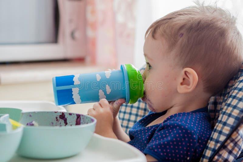 Behandla som ett barn i köket som dricker fruktsaft eller, mjölka, vitaminer och hälsa fotografering för bildbyråer