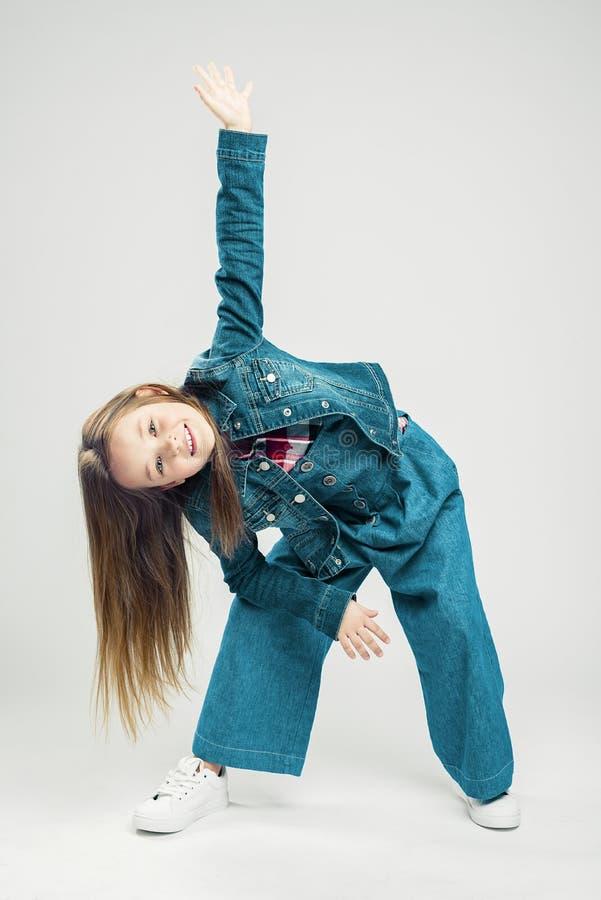 Behandla som ett barn i r?relse ungemodelilla flickan gör rörelse med hennes armar och ben barns dans bakgrundsborsteclosen isole arkivbilder
