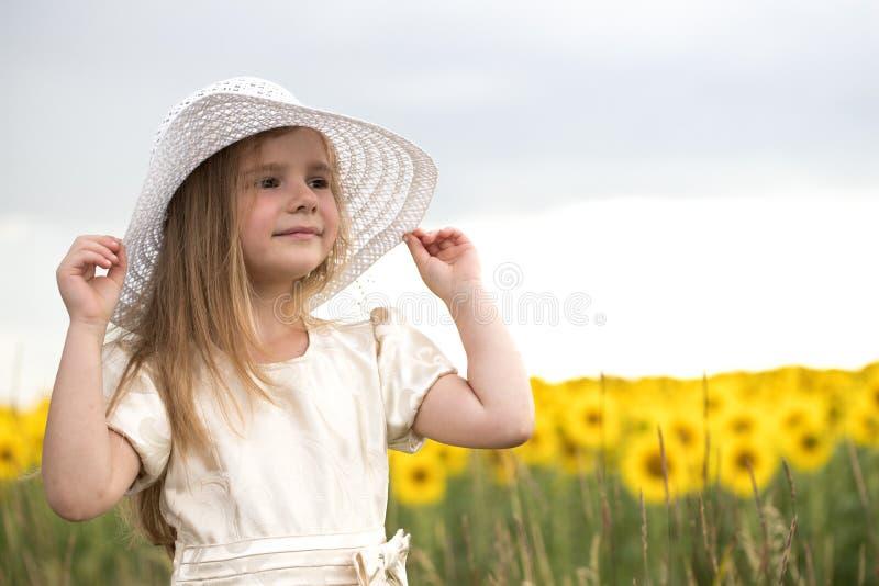 Behandla som ett barn i solrosor flickan i en hatt går på ett fält med blommor royaltyfri bild