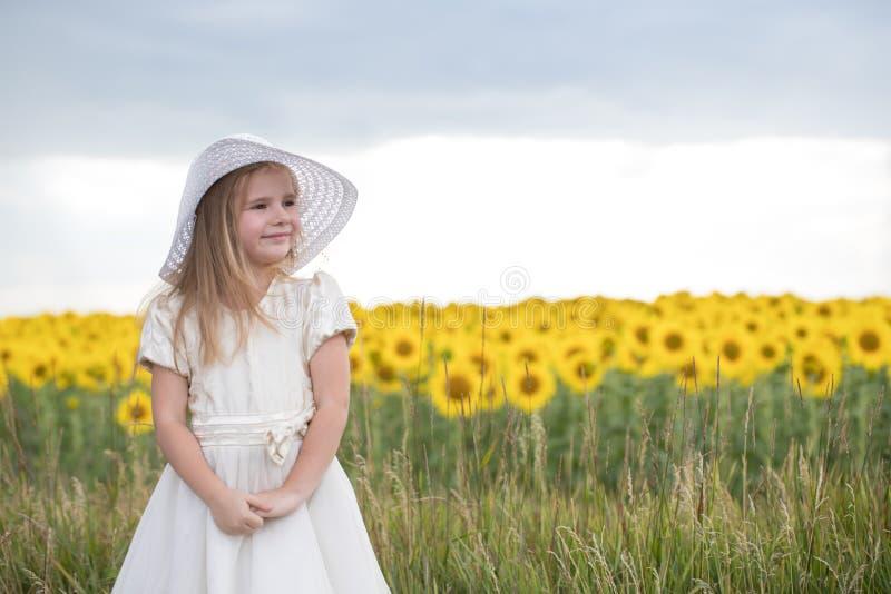 Behandla som ett barn i solrosor flickan i en hatt går på ett fält med fl owers royaltyfri foto