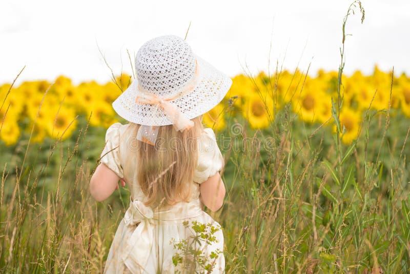 Behandla som ett barn i solrosor liten flicka på fältet med blommor royaltyfria foton