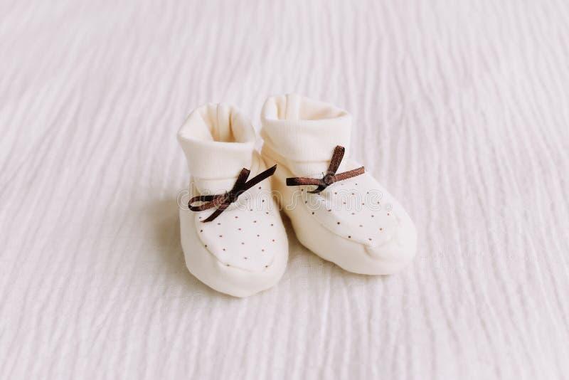 Behandla som ett barn kängor för ` s på vit bakgrund Att vänta på behandla som ett barn vita skor för nyfött på en pastellblåttba royaltyfria foton