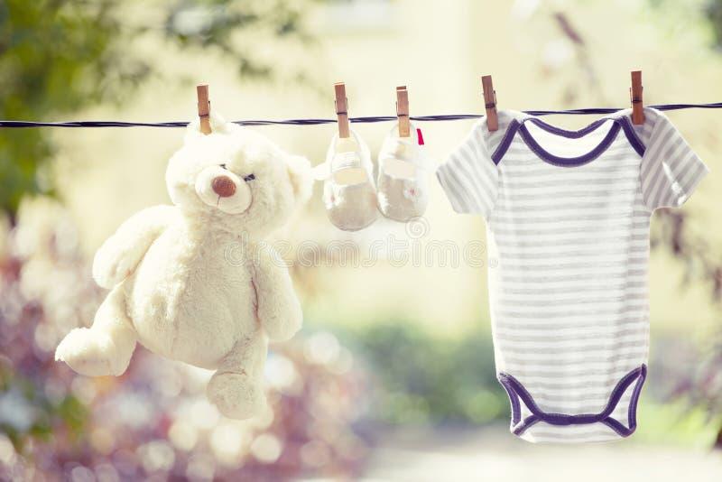 Behandla som ett barn kläder, kängor och nallen som hänger på klädstrecket royaltyfri foto