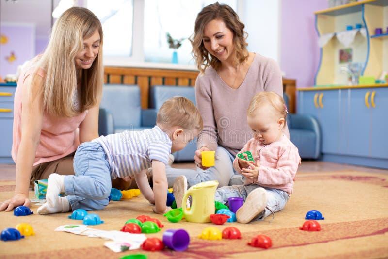 Behandla som ett barn krypande och att ha gyckel på golv i barnkammare Mödrar spelar med barn i daghem royaltyfri bild