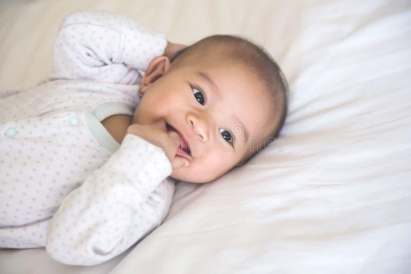 Behandla som ett barn le att ligga på en säng royaltyfri bild