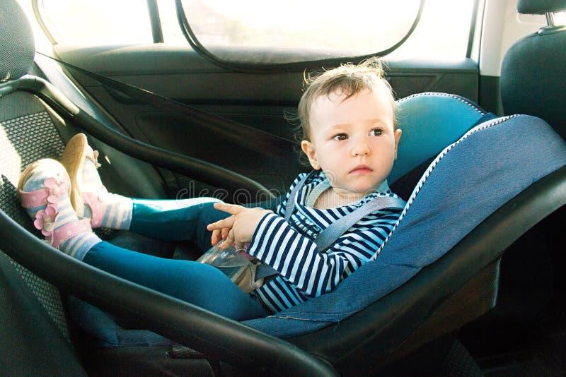 Behandla som ett barn leendet i ett säkerhetsbilsäte Säkerhet en årig barnflicka i blåttkläder sitter på auto vagga Regler för no arkivfoto