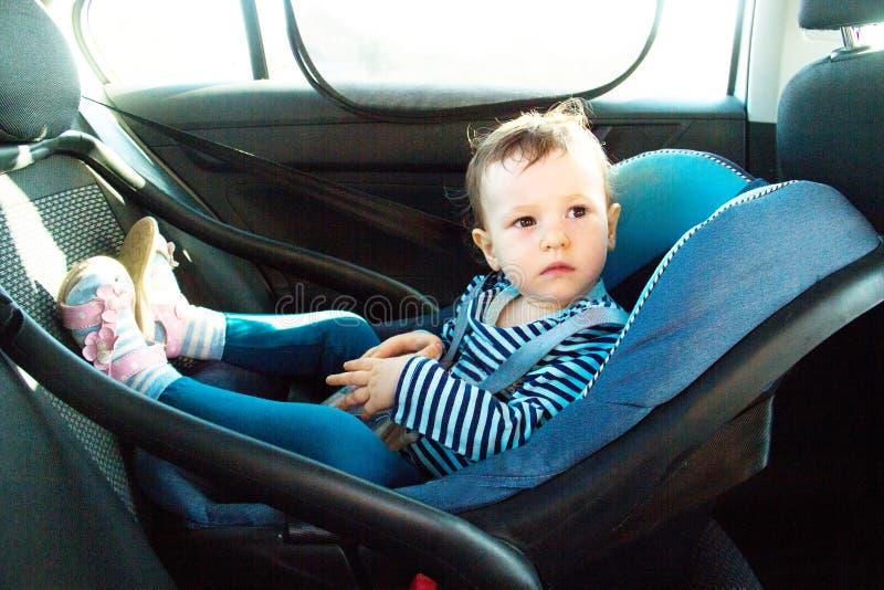 Behandla som ett barn leendet i ett säkerhetsbilsäte Säkerhet en årig barnflicka i blåttkläder sitter på auto vagga Regler för no royaltyfria bilder