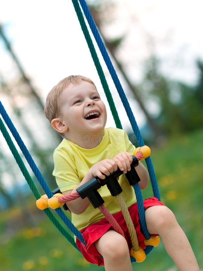 behandla som ett barn leka swing för pojken royaltyfri foto