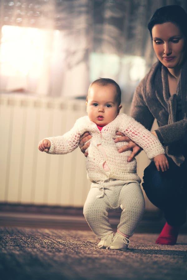 Behandla som ett barn lite att lära att gå med moderhjälp hemma fotografering för bildbyråer
