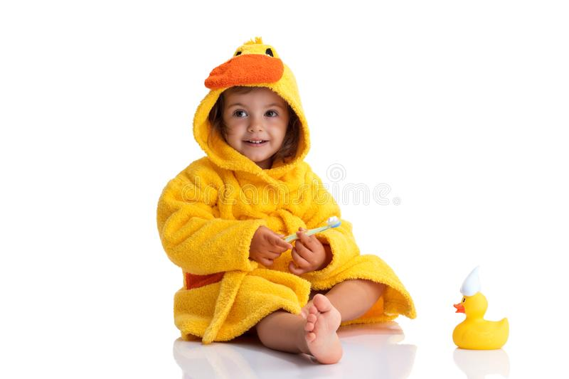 Behandla som ett barn lite att le under en gul handduk och att borsta hans tänder royaltyfria foton