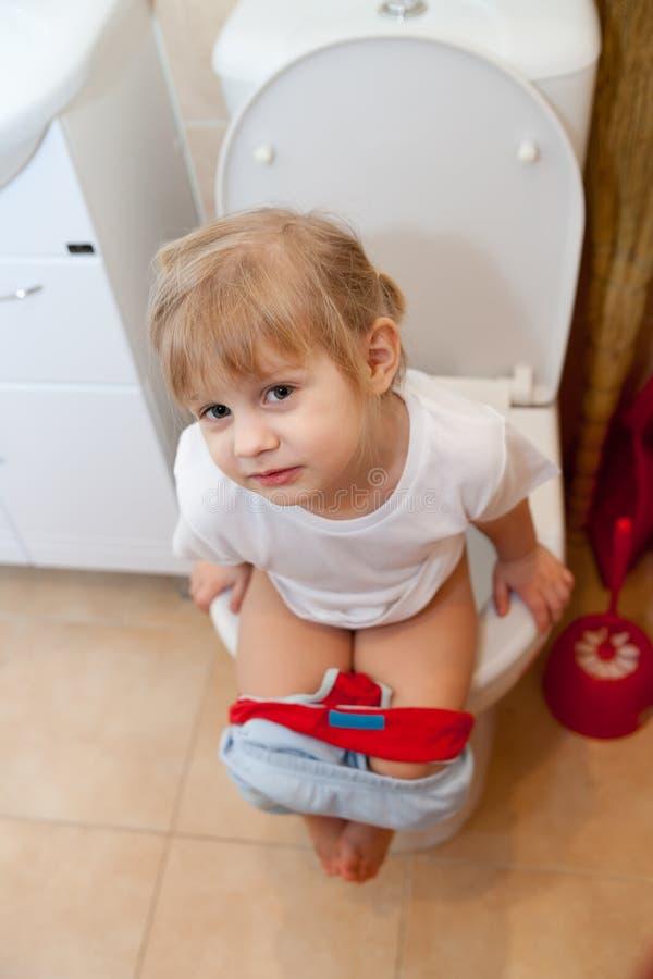 Behandla som ett barn lite att pissa på toalett arkivbilder