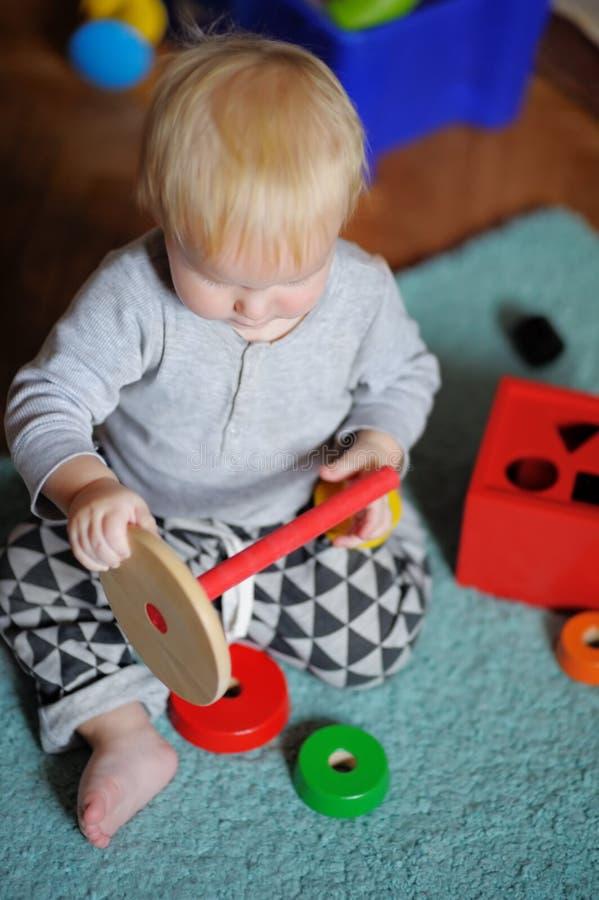 Behandla som ett barn lite att spela med leksaken arkivbild