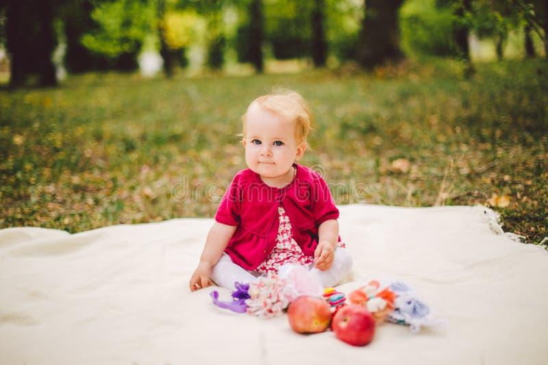 Behandla som ett barn lite Caucasian etnicitet för flickan som blond som är årig från födelse, sitter på en pläd på grönt gräs i  royaltyfri fotografi