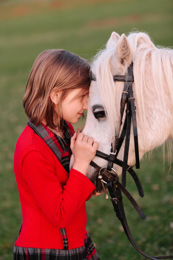 Behandla som ett barn lite den lilla vita hästen för flickan som ser de royaltyfria foton